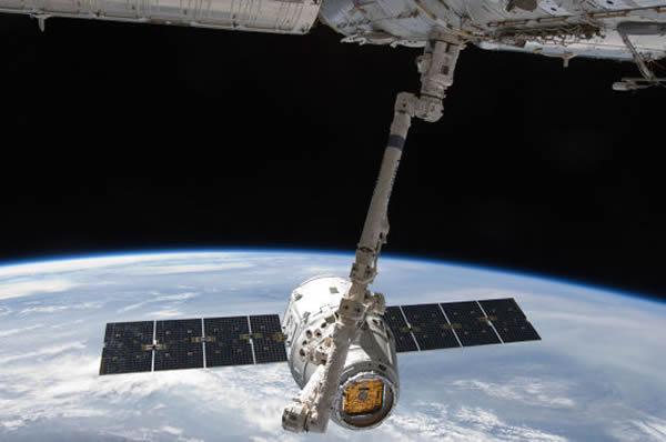 资料图:龙飞船正逐渐接近国际空间站,以便空间站上的机械臂可以将其捕获并转移至相应的对接平台。