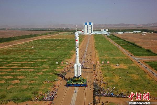 承载着组合体的活动发射平台缓缓驶出载人航天发射场垂直总装测试厂房,安全转运至发射塔架。