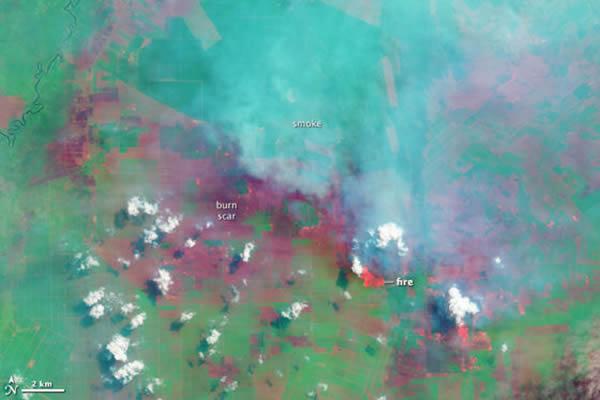 Landsat 8卫星2013年6月25日拍下了上面的第一幅照片,显示了剧烈的火灾现场。 <br>在这幅伪色照片中,烟雾呈现为蓝色,高处的云呈现为白色。 <br>橙色的是火光,暗红
