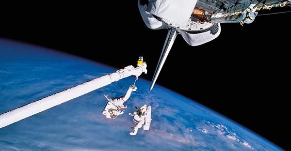 1994年9月,宇航员卡尔•米德和马克•C李在轨道上作业的情景,该任务中宇航员对背包系统进行测试