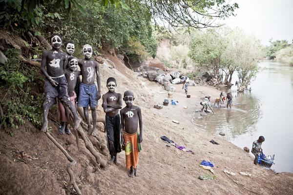 塞内加尔境内冈比亚河沿岸的男孩。他们用白色颜料把脸涂成骷髅模样,胸前写着足球队服上的号码做装饰。