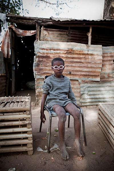 冈比亚河沿岸乔治小镇里的一个男孩,坐在母亲的咖啡店外,带着塑料眼镜玩耍。