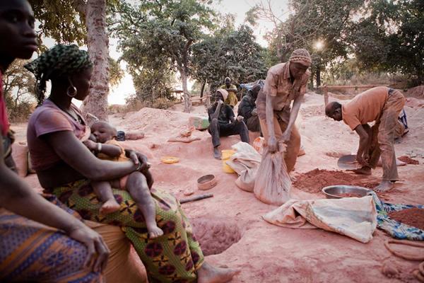塞内加尔境内一处不受监管的金矿里,男矿工正在淘沙,女矿工正在给孩子喂奶。
