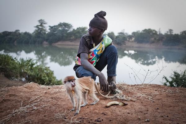 男孩穆萨·加罗(Musa Jallow)和他的宠物小赤猴。小赤猴的母亲已经被猎人杀死了。