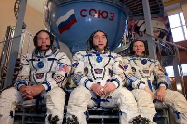 """2014年3月5日,美国宇航局宇航员史蒂文-斯旺森(右)与俄罗斯宇航员亚历山大-斯科沃尔佐夫(中)和奥雷格-阿尔特米耶夫一起,坐在俄罗斯郊外星城里的一个""""联盟T"""