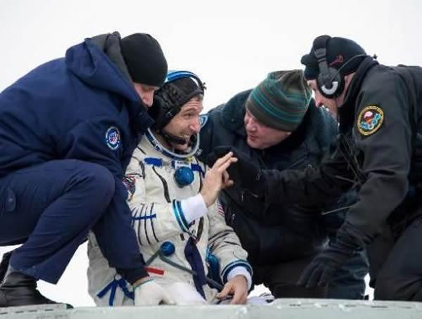 """美国宇航局2014年3月11日拍摄并公布的这张照片显示,""""联盟TMA-10M""""号降落在热孜卡兹甘附近的哈萨克大草原上后不久,美国宇航员迈克尔-霍普金斯在被人从太"""