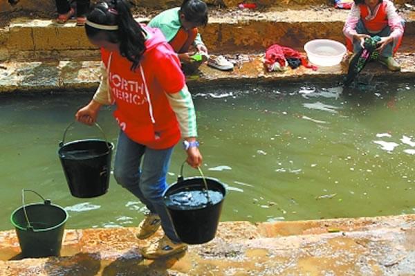 女孩儿们在村边池塘洗衣服,之后打水带到学校冲厕所。