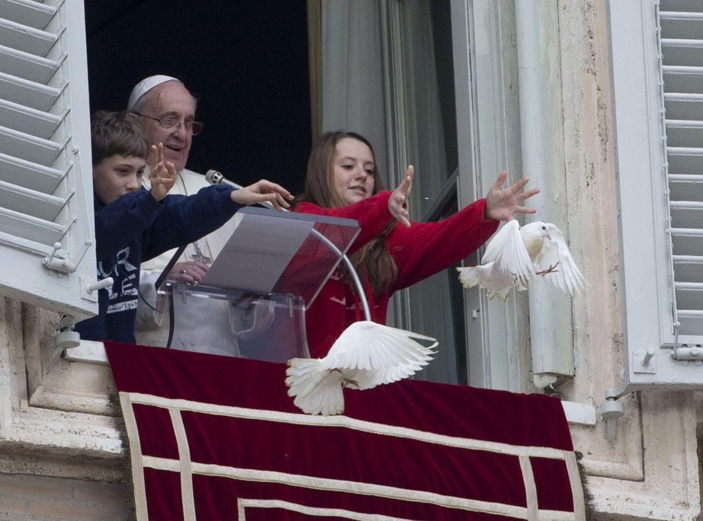 教宗方济各在他俯瞰圣彼得广场的播音室窗口和两名孩童一起释放鸽子