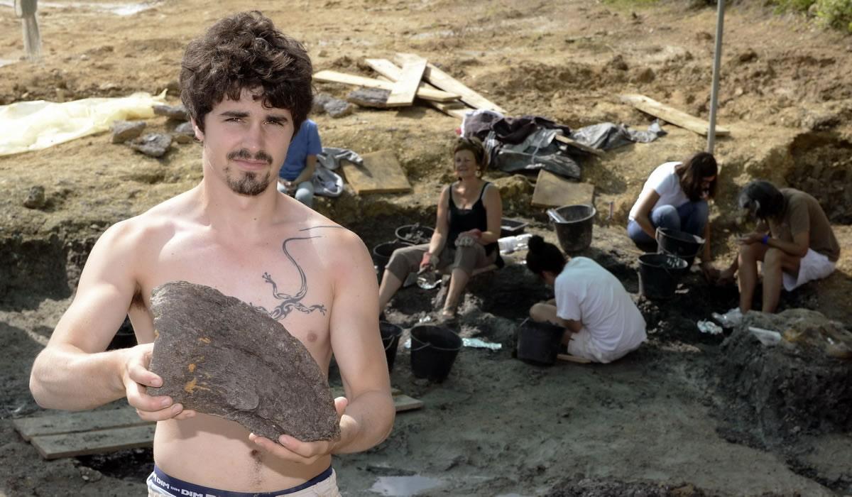 7月29日, 在法国昂雅克-夏朗德,游客观看学生和志愿者在挖掘现场寻找恐龙化石。