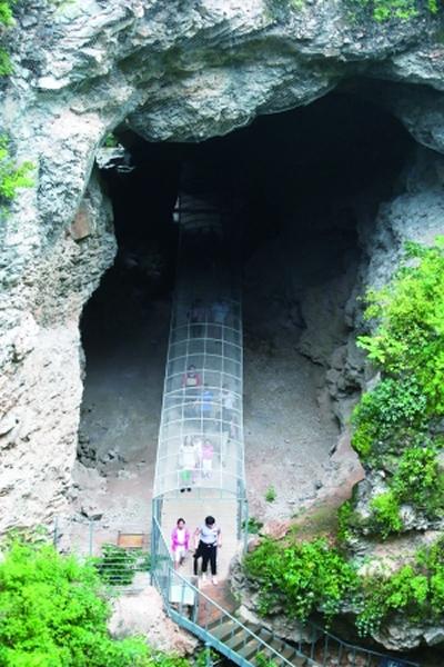 游客在猿人洞鸽子堂洞口参观。鸽子堂是周口店北京人遗址中猿人洞的一部分。