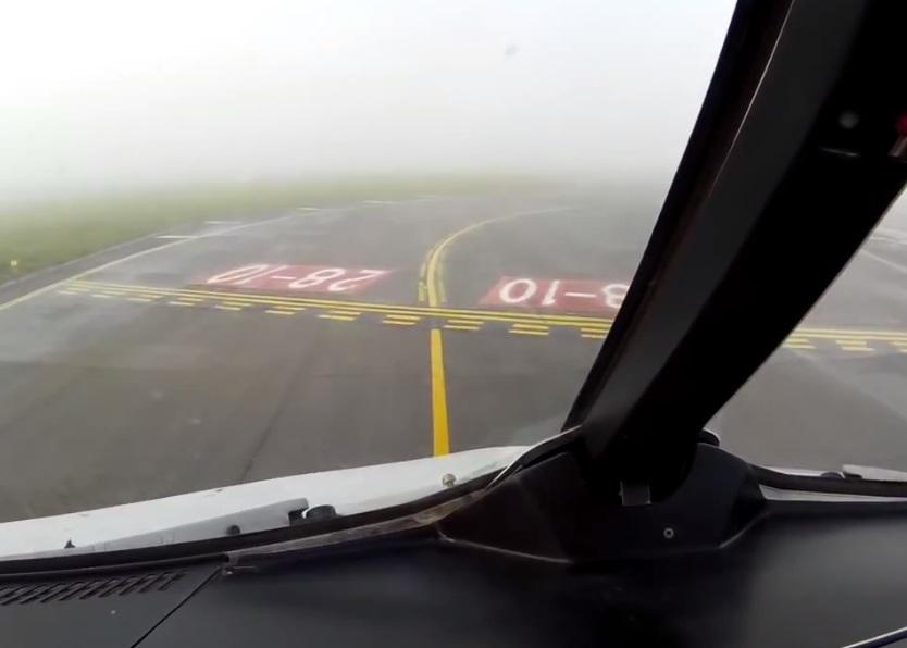 飞机安全降着陆后在跑道上滑行,稍远处视野仍被大雾遮掩。
