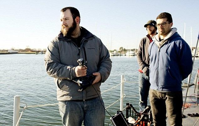 研究员用操控杆,控制机械鱼在水中进行监控任务。