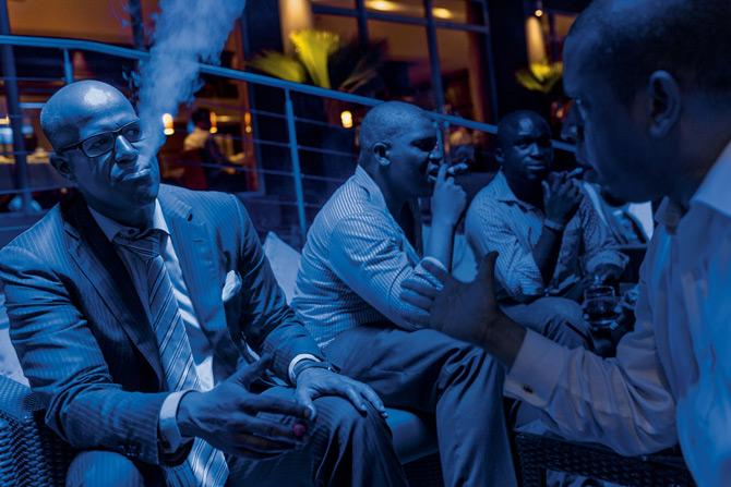 拉哥斯的上层阶级正在快速扩张,其中包括拉哥斯雪茄俱乐部的这些年轻商人,他们在维多利亚岛上的一家饭店享受片刻悠闲。