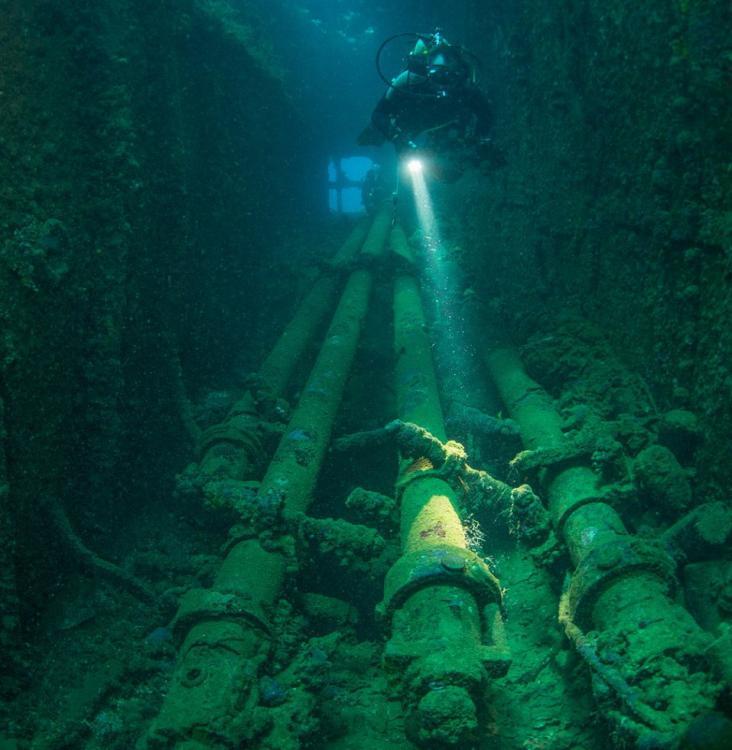 """一名潜水员正探查""""平安丸""""号(Heian Maru)残骸上的潜望镜。"""