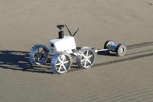 """2013年年底,日本Hakuto 团队正在滨松的海岸边对他们名为""""Moonraker""""的小型轻质月球漫游车进行测试,它的后面用伸缩杆连接着另一辆名为""""Tetri"""