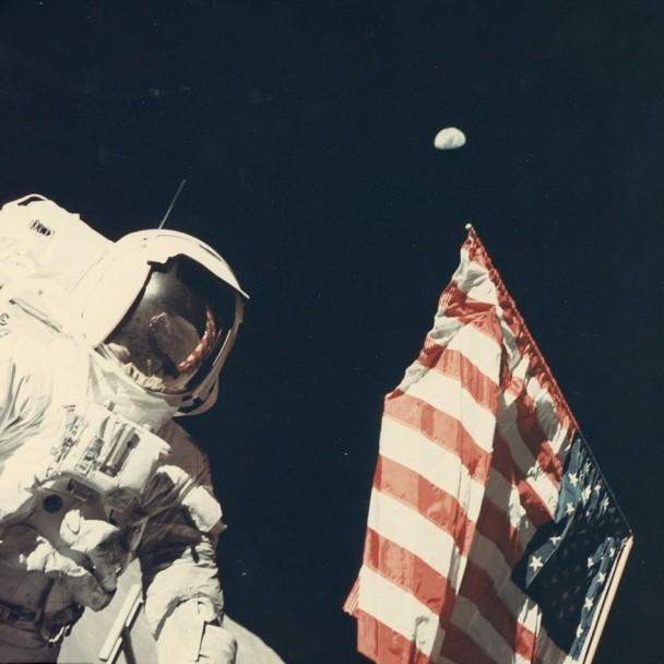 美国太空人将国旗置于地上,地球在天空高挂。