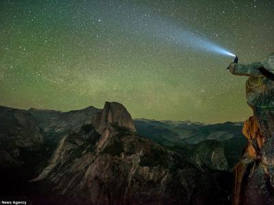 """观星者坐在美国加州约塞米蒂国家公园著名""""冰川点""""边缘处头戴照明灯观赏美丽星空"""