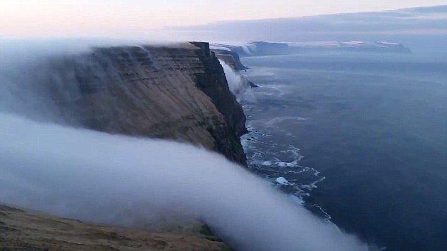 冰岛布雷扎峡湾罕见自然奇观:山顶浓雾如瀑布一般流下海崖