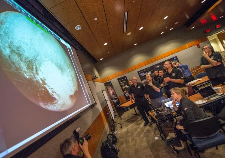 新视野号科学小组成员聚精会神观看探测器见到的冥王星最光亮的照片。