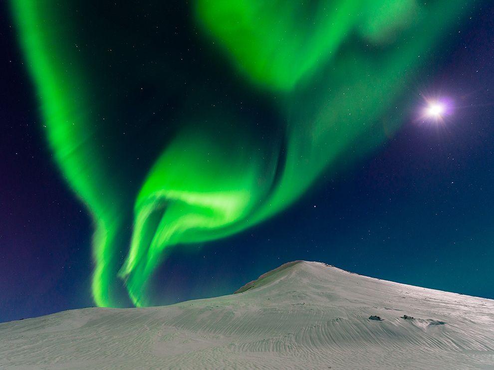 北极光与一轮明月同时出现在冰岛的夜空