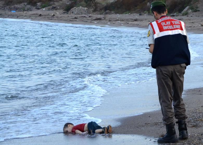 小男孩遗体被冲上岸,警员走近察看。