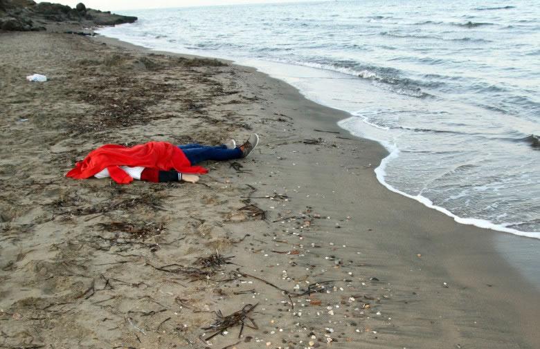 沙滩上躺着另一具年轻难民的尸体