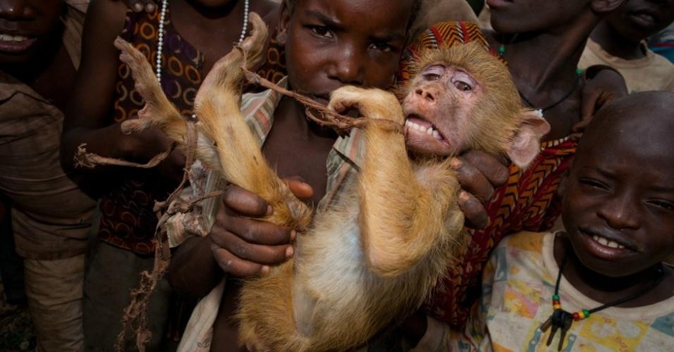 痛心一幕:非洲莫桑比克小孩出售被捕捉到的惊恐黄狒狒