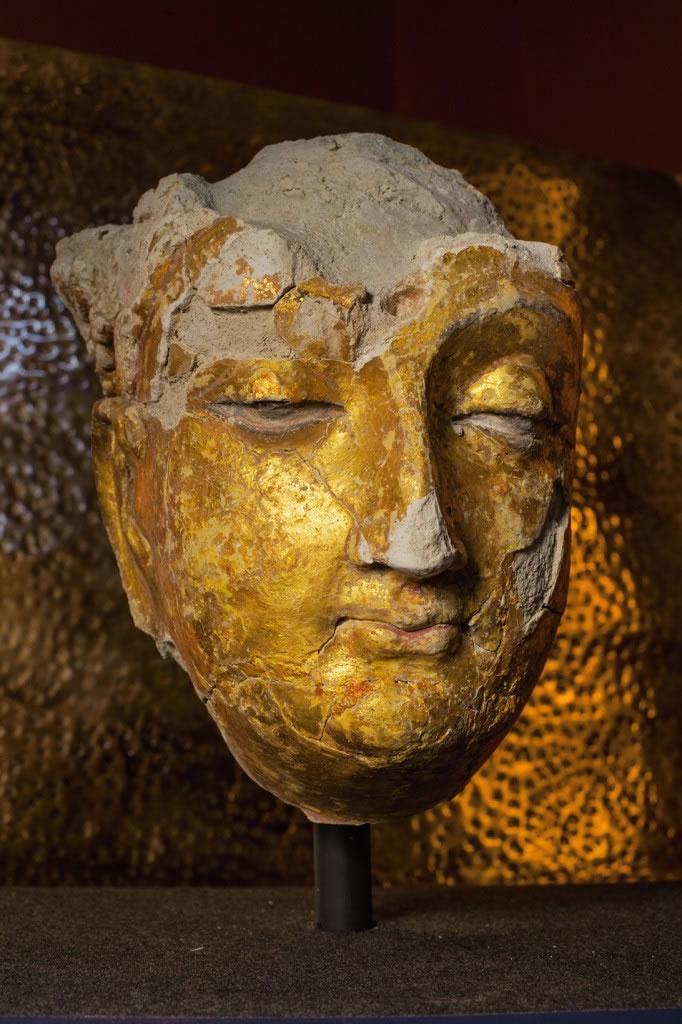 古老的面孔唤起了艾娜克遗址曾是中亚十字路口的过往;其中有镀金石膏的佛陀面孔,高20.3公分。 Photograph by Simon Norfolk