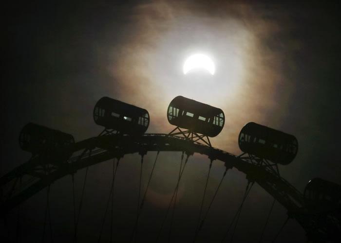 半遮蔽的太阳落在新加坡摩天观景轮旁边,形成一幅美丽的画像。