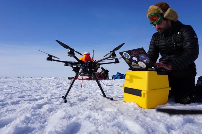 一名阿拉斯加无人机系统整合中心的研究生正在操作空拍机,针对紊乱的冰原进行测绘,协助当地猎人开辟雪地摩托车路线以便前往捕鲸。 PHOTOGRAPH BY ALAS