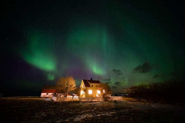 北极光照亮挪威房舍上的天空。 PHOTOGRAPH BY SERGIO PITAMITZ, NATIONAL GEOGRAPHIC CREATIVE