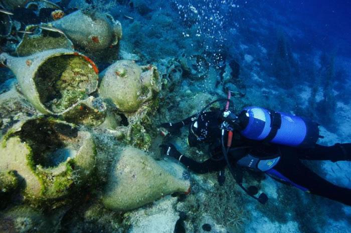 一名潜水员正在测量在最近发现的45艘船骸中、最古老的船只上所发现的萨摩亚双耳罐。这些陶罐可追溯至公元前525年至480年间。 PHOTOGRAPH BY VAS