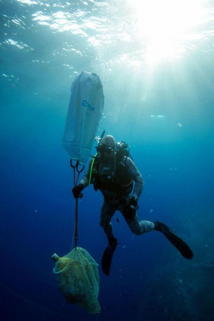 潜水渔夫米缇克斯(Manos Mytikas)从海底捞起一个双耳罐。许多从这艘沉船上发现的物件都来自于北非。 PHOTOGRAPH BY VASILIS MEN