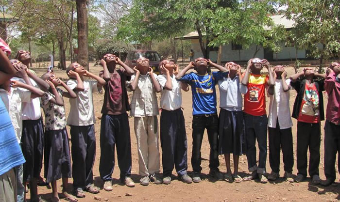 2013年,学生们利用日食眼镜,安全观赏日食。 PHOTOGRAPH BY CHUCK AND SUE RUHLE
