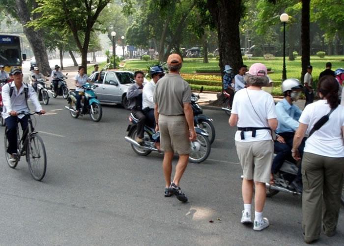 外地人来到越南需学会在车辆中,找到时机过马路。