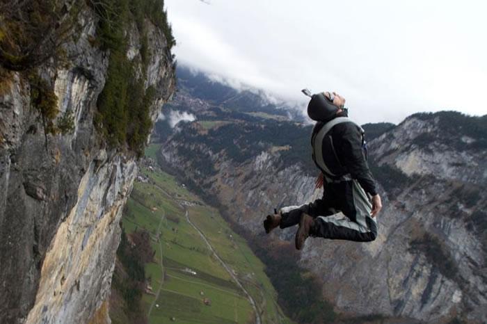一位定点跳伞运动员在悬崖边后空翻。 PHOTOGRAPH BY OLIVER FURRER, ALAMY PHOTO