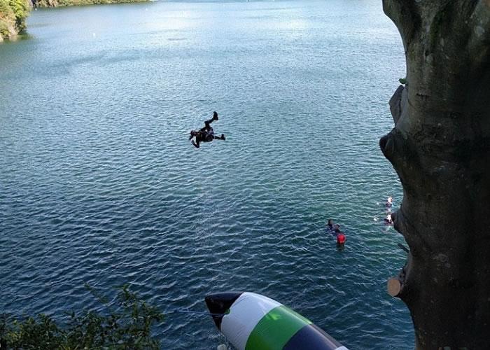 坐在巨型浮床上的人被弹飞上高空再堕入湖中。