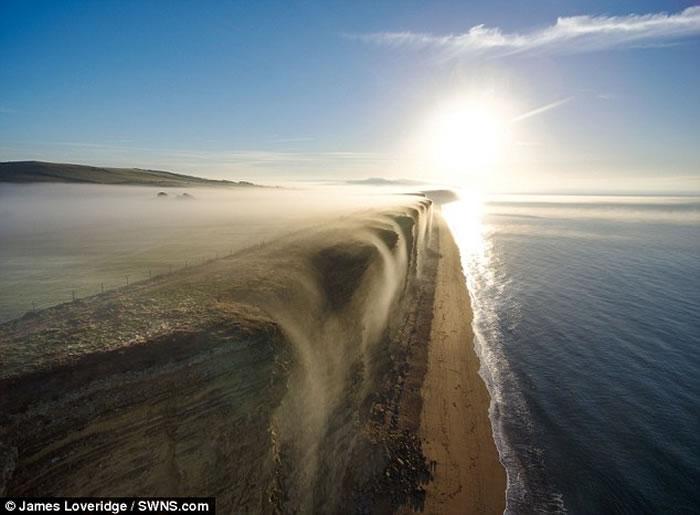 英国多塞特郡西湾出现奇特自然现象 一片白雾在崖边如瀑布向下飞泻