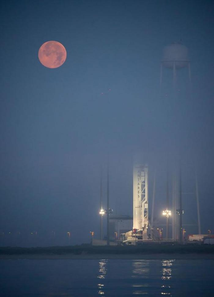 2014年6月12日维吉尼亚州的瓦劳埔飞行中心,天体轨道科学公司天蝎号火箭(Antares rocket)后方,浓雾中的满月依然吸睛。 / Photograph