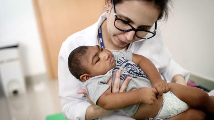 孕妇受寨卡病毒感染,孩子出生时未必一看便知有健康问题。图为巴西女医生为一名小头症婴儿做物理治疗。