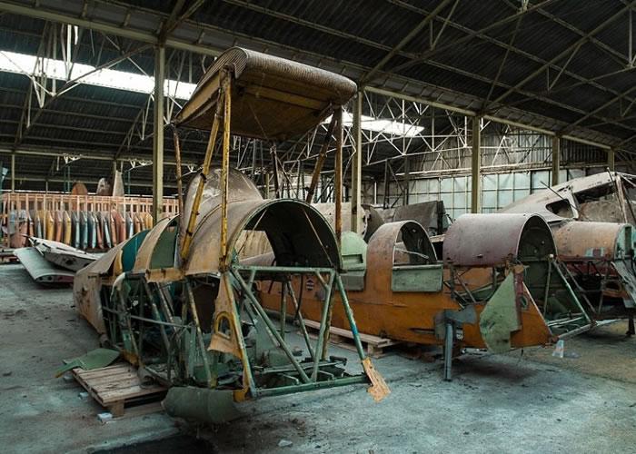废弃的机库停放了飞机、机翼和引擎等零件。