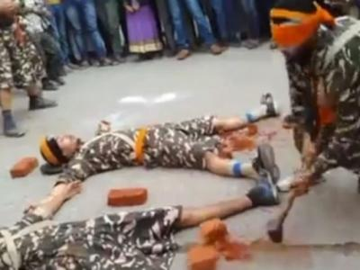 印度3名男子躺在地上亡命演出 蒙眼男重锤击头边砖