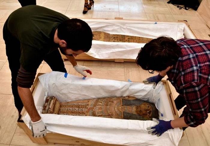 在埃及驻华府大使馆举行的文物归返典礼上,工作人员从箱中搬出一具幼童棺。该文物由走私进入美国,将被送回开罗。 PHOTOGRAPH BY KENNETH GARR