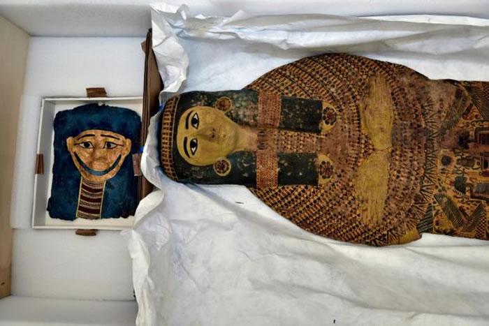 一枚埃及镀金木乃伊面具(左)放在棺木旁。这两件骨董皆被非法偷渡到美国,并即将运回目前兴建中的大埃及博物馆。 PHOTOGRAPH BY KENNETH GARR