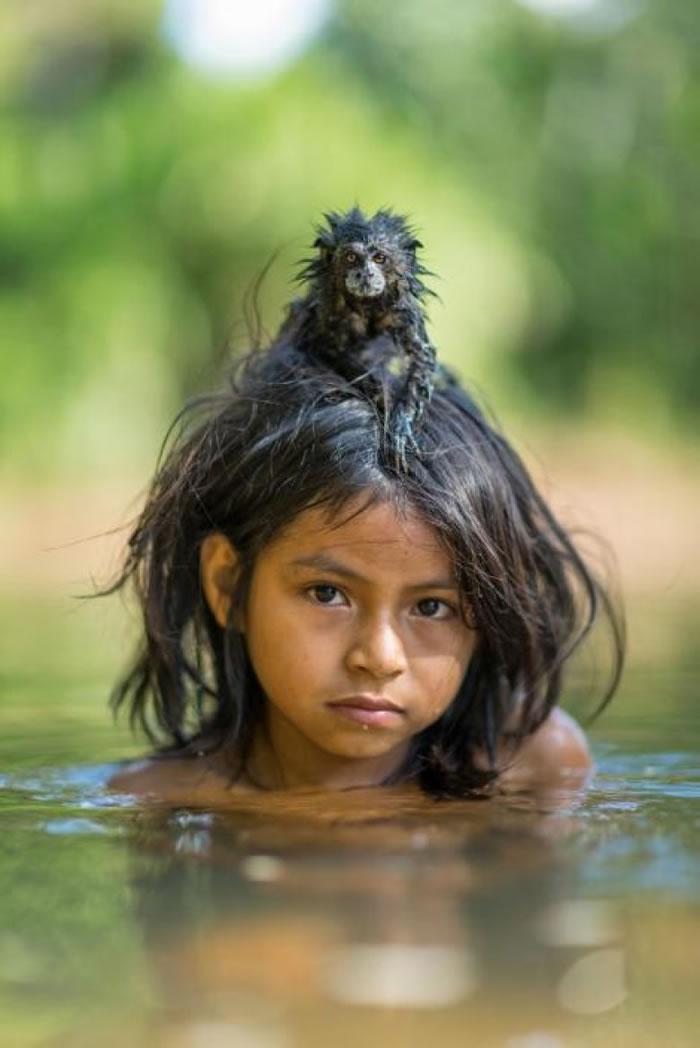 秘鲁马努国家公园保护区原住民小孩与小猴子。