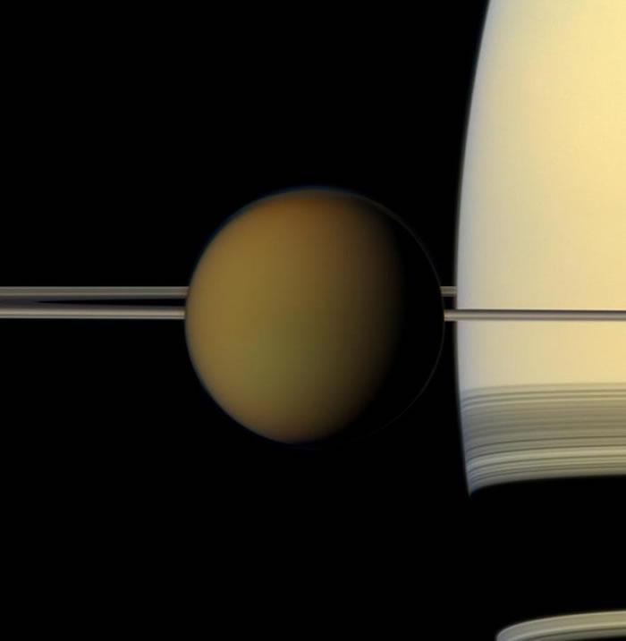 从这张美国航太总署(NASA)卡西尼号太空船所拍摄的全彩影像中,可以看到土星最大的卫星——土卫六,正经过土星和土星环的前方。 PHOTOGRAPH BY NAS