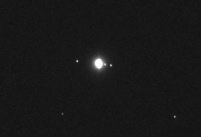 """图中显示""""奥里西斯- REx""""探测器最新拍摄的图像,中心位置是木星,右侧是木卫一和木卫二,左侧是木卫四,木卫三是木星第四大卫星,也出现在这张图像中,但由于运行至"""