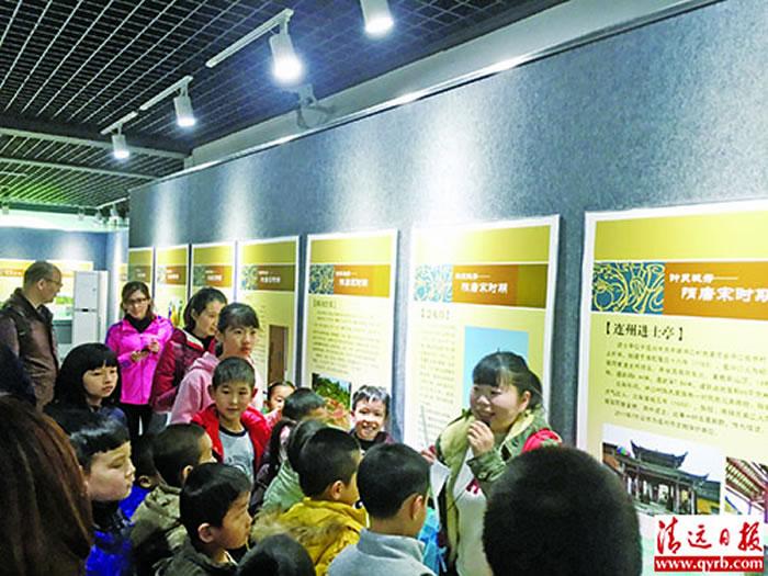 """清远市博物馆""""北江文明展"""",孩子们认真听工作人员讲解。清远日报记者 岳超群 摄"""