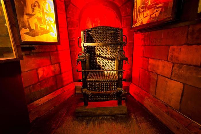 酷刑博物馆中恐怖的宗教法庭座椅陈列室,展示了放大的古籍图片,并有文章说明这种座椅的历史和使用方式。 PHOTOGRAPH BY MICHIEL VAARTJES
