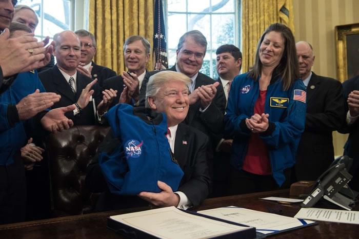 特朗普签署法案后,喜孜孜地展示一件太空衣。
